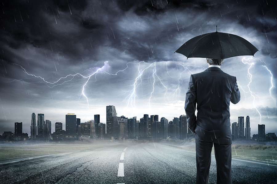 Commercial Umbrella Insurance - View of Businessman Standing on the Street Holding an Umbrella Looking at the City