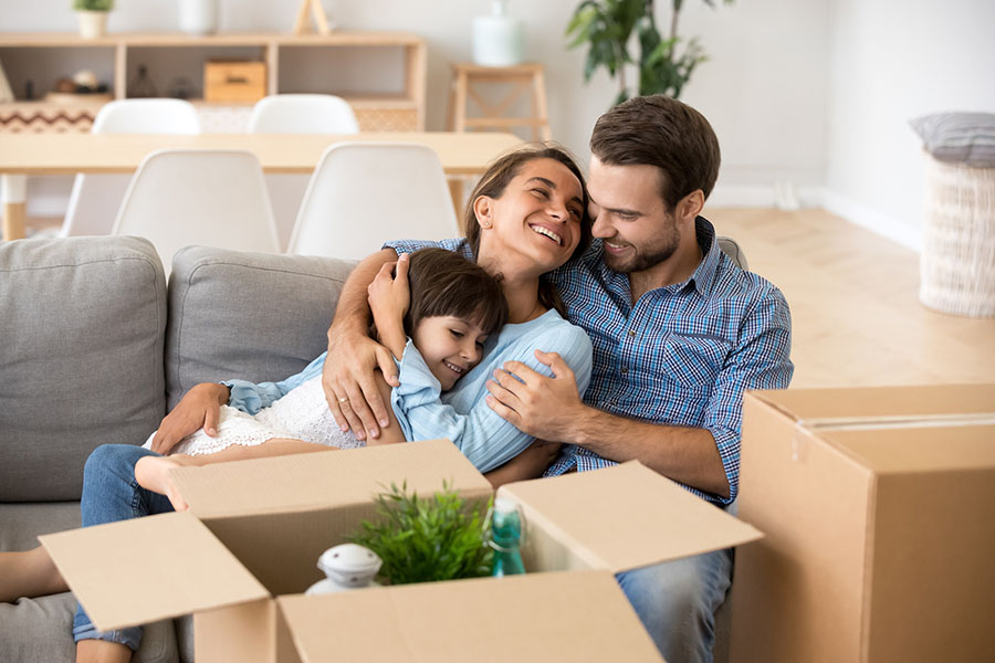 Personal Insurance - Happy Family Sitting on the Couch Enjoing Their New Home